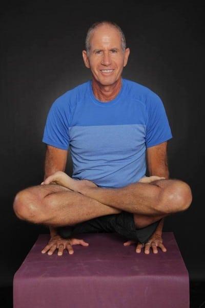 Hombre practicando yoga con 62 años -
